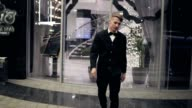 Attractive young man in a black suit walking out of a hotel in the evening. Behind a lot of blurred lights and glass door of luxurious hotel video