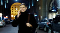 Attractive young man talking on an evening street, talking on the phone video