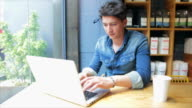 Attractive young man using laptop in a coffee shop. video