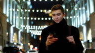 Attractive young man walking on a night city: looking at the phone screen video
