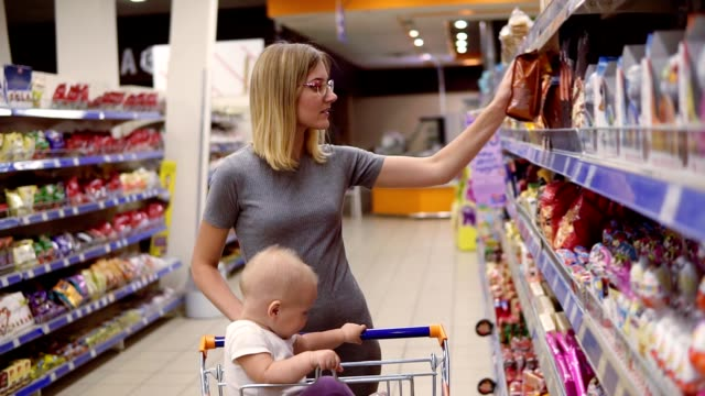 Attractive young mother is choosing sweets and cakes in the supermarket, while her little baby is sitting in a grocery cart. Family shopping time video