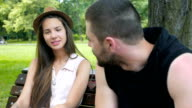 Attractive young woman and man having a conversation in the park video