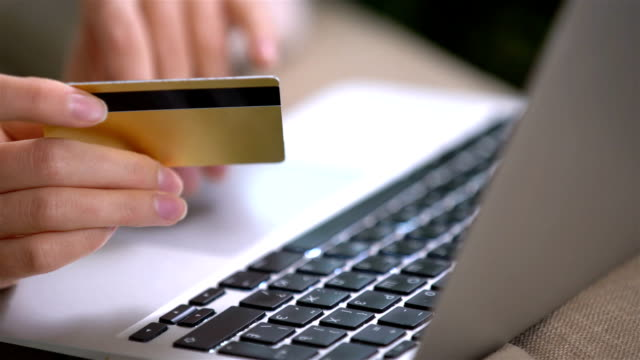 Attractive young woman doing online purchases uses gold credit card video