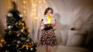 Attractive young woman gives golden gift ribbon box into camera video
