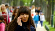 Attractive young woman in blue coat talking on the mobile phone in the alley in the park. Happy girl talking on smartphone, outdoors. Close-up video