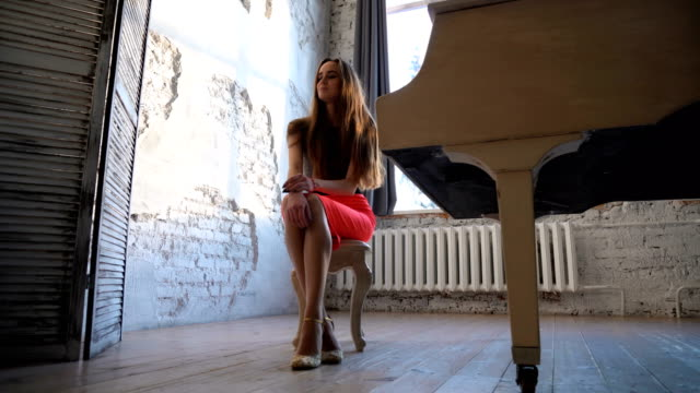 Attractive young woman in evening dress sitting at the white grand piano video