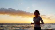Attractive young woman is running along the seashore at sunset. Engage in sports - healthy lifestyle. Steadicam slow motion shot video