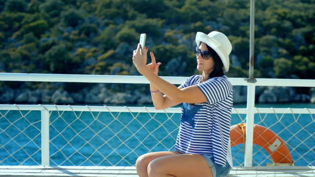 Attractive young woman on yacht taking a selfie photo video