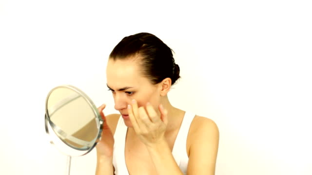 Attractive young woman searching for pimples in the mirror video