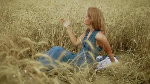 Attractive young woman sitting in the golden wheat field. Her hand is touching wheat ears. Harvest concept. Harvesting. Slow motion shot video