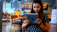 Attractive young woman using digital tablet touchscreen computer in cafe video