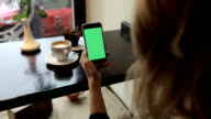 Attractive young woman using her green touch screen mobile cell phone in cafe video