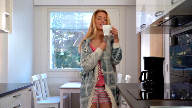 Attractive young woman with coffee in the morning kitchen. Slow motion. video