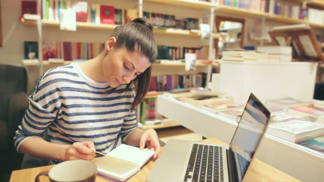 Attractive young woman working on the laptop in the bookstore video