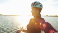 Attractive young women cyclist taking selfies at sunset. video