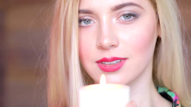 Attractive young women with candle in arms. Never again. Feels sedness and looks in camera video