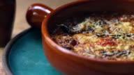 Aubergine, feta and tomato bake in earthenware dish, zoom video