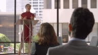 Audience applaud young woman speaking at a business seminar video