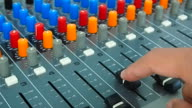 Audio Engineer adjusting faders on mixing console desk video