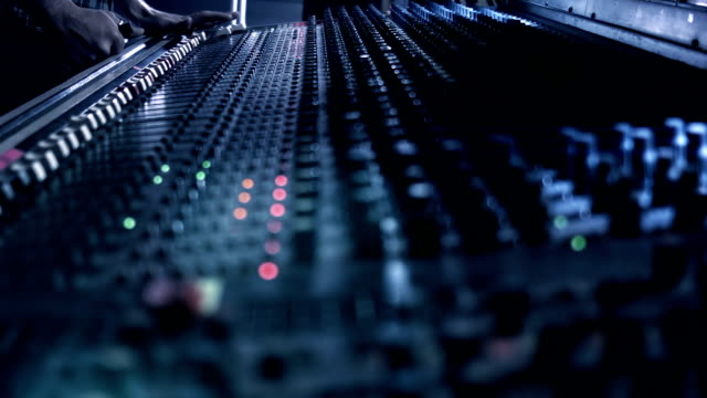 Audio Engineer adjusting knobs and faders on his mixing console desk during a live event. video