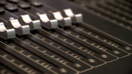 Audio mixing console fader automation medium shot with rack focus video
