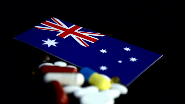 Australian flag with lot of medical pills isolated on black background video
