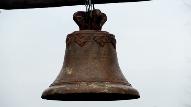 Authentic medieval church bell covered with rust, ancient symbol of video