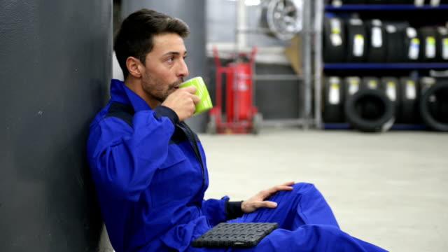 Auto mechanic having a coffee break video