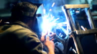Automaster weld the frame of a custom motorcycle in the garage video