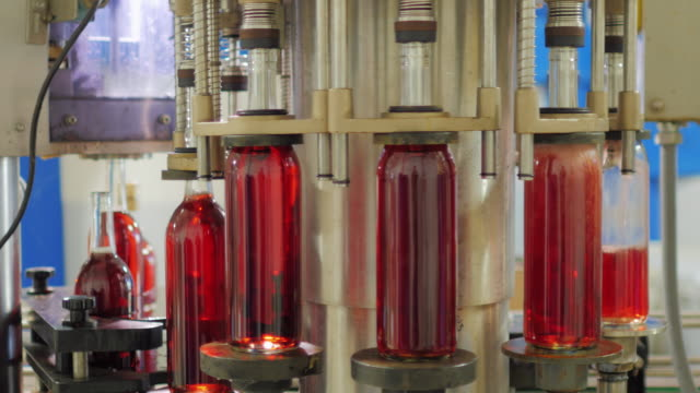 Automation in the winery. On the conveyor poured red wine in the bottle video
