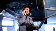 Automotive mechanic using a laptop and phone video