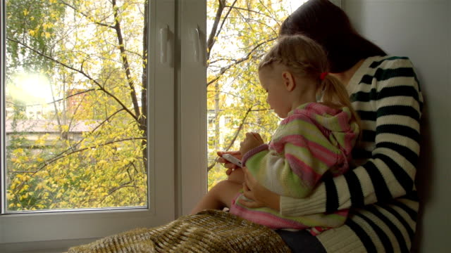 Autumn day, mother and daughter playing on the windowsill in the smartphone. video
