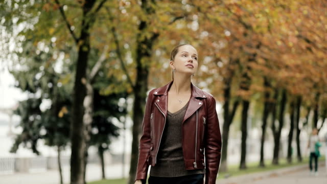 Autumn is coming. Elegant woman in burgundy leather jacket walk in city street, slowmotion video