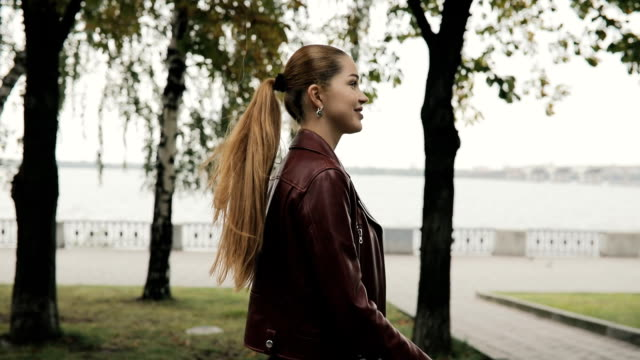 Autumn is coming. Happy woman in burgundy leather jacket walk in city street, slowmotion video