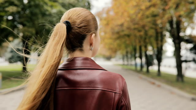 Autumn is coming. Pretty woman in burgundy jacket walk in city street, slowmotion, rear view video