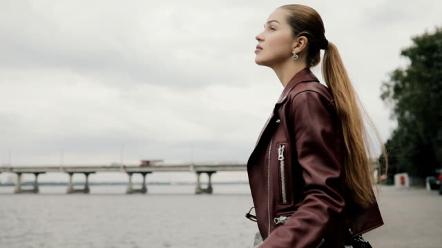 Autumn is coming. Woman in burgundy jacket looks at river and cloudy sky, slowmotion video