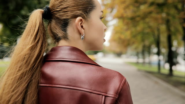 Autumn is coming. Woman in burgundy jacket walk in city street, slowmotion, rear view video