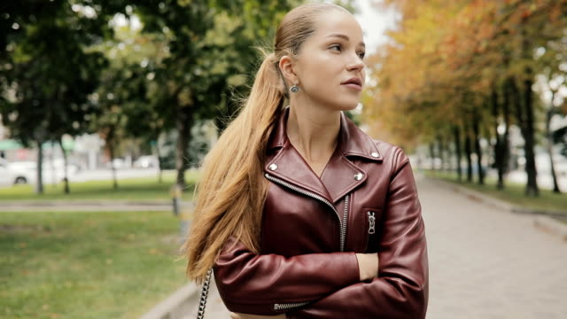 Autumn is coming. Woman in burgundy leather jacket walk in city street, slowmotion video