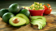 Avocados whole and sliced on wooden chopping board. video