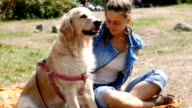 Awesome golden retriever dog being petted by it's female owner outdoors video