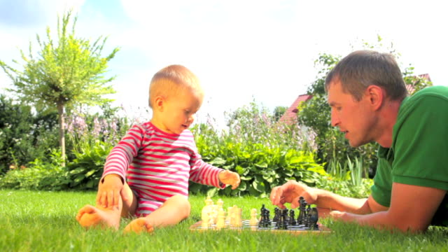 Baby and father playing chess in the garden video
