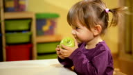 Baby and food, little girl eating green apple at school video