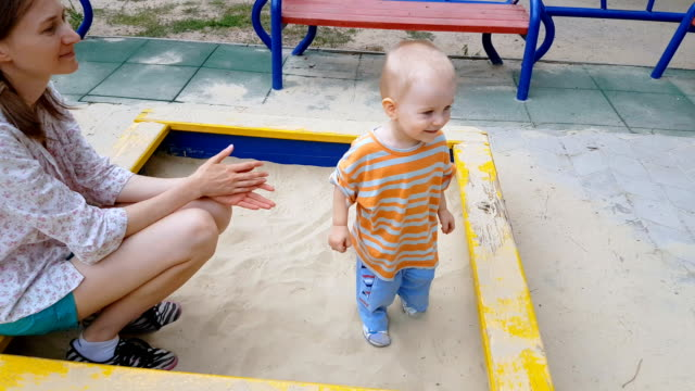 Baby and mom playing in sandbox video