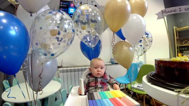 Baby boy celebrates its first birthday. He sits in a chair and playing wooden Boards. Against the background of balloons. video