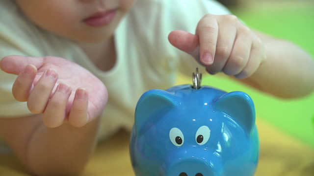 Baby boy inserting a coin into a piggy bank, indoor financial concept. video