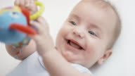 Baby boy laughing and putting a toy in his mouth video