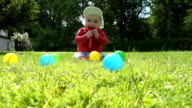 baby boy sit on meadow grass between colorful balls and play. video