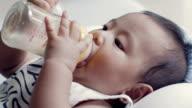 Baby boy sucking nursing bottle. video