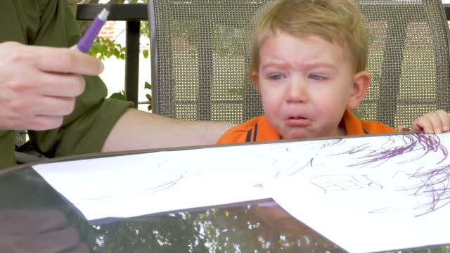 A baby boy with a sad face waiting for his dad to hand him a pen video