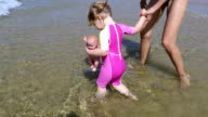 baby doll and mom playing with waves video